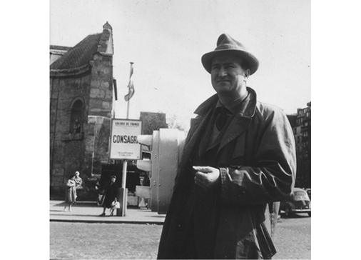 Consagra standing in front of the poster of his personal  exhibition at the Galerie de France, Paris, 1959